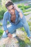 Den tillfälliga mannen sitter huka sig ned utomhus Arkivbilder