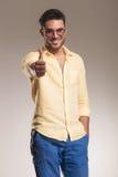 Den tillfälliga mannen som ler visa tummarna gör en gest upp Royaltyfri Foto