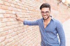 Den tillfälliga mannen står med handen på tegelstenväggen Royaltyfri Fotografi