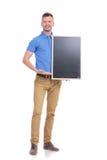 Den tillfälliga unga mannen framlägger svart tavla Royaltyfri Foto