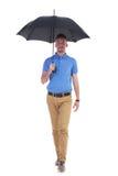 Den tillfälliga unga mannen går till dig med paraplyet Arkivbild