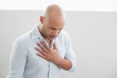 Den tillfälliga unga mannen med bröstkorgen smärtar Royaltyfri Foto