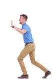 Den tillfälliga unga mannen skjuter något som är imaginär Arkivbild