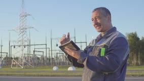 Den tillfredsställda elektrikeren jublar i framgång Tekniker och arbetare på den elektriska avdelningskontoret Arbetare med minne stock video