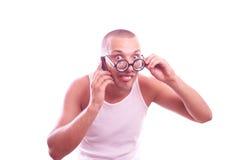 Den tillfredsställda nerden i glasögon stannar till mobiltelefonen arkivbild