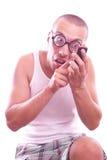 Den tillfredsställda nerden i glasögon stannar till mobiltelefonen royaltyfri fotografi