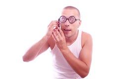 Den tillfredsställda nerden i glasögon stannar till mobiltelefonen royaltyfri foto