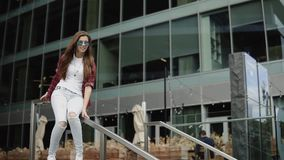 Den tillfredsställda unga lyckliga flickan i moderiktig kläder och exponeringsglas sitter på ledstängerna nära kontorsmitt arkivfilmer