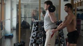 Den tjocka nykomlingen med hjälp av en lagledare gör squats med skivstången lager videofilmer