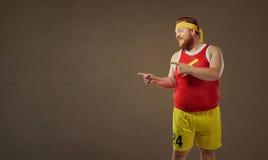 Den tjocka roliga mannen i sportar beklär punkter med hans finger Royaltyfri Bild