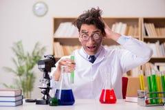 Den tokiga galna forskaredoktorn som gör experiment i ett laboratorium arkivfoto