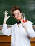 Den tokiga professorn beundrar hans experimentella röda flytande Arkivbild