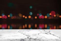 Den tom vit marmortabellen och bokeh på natten tänder arkivfoton