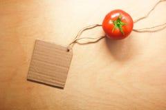 Den tomatgrönsaken och prislappen på wood bakgrund texturerar Royaltyfria Foton
