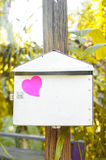 Den tomma anteckningsboken eller klibbiga anmärkningar som är rosa på stolpen, boxas med solljuslodisar royaltyfri fotografi