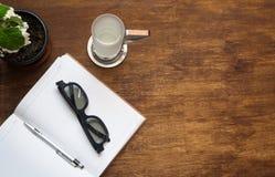 Den tomma anteckningsboken med svarta exponeringsglas, pennan och exponeringsglas av vatten är på Royaltyfri Foto