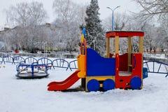 Den tomma barnlekplatsen i vinterstad parkerar Royaltyfri Foto