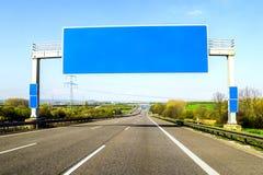 Den tomma blåa motorvägen undertecknar över vägen på solig dag arkivbild