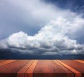 Den tomma bruna träbilden för bakgrund för tabellyttersida och för clouhimmel suddiga, för produktskärmmontage, kan användas för  Royaltyfri Bild