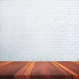 Den tomma bruna trätabellyttersida och vitväggen gör suddig bakgrundsbild, för produktskärmmontage, kan användas för montage elle Royaltyfri Fotografi