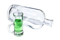 Den tomma genomskinliga flaskan och ett exponeringsglas fyllde med en grön absint Royaltyfria Bilder