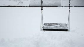 Den tomma gungaleksaken i parkerar på vinter, och den snöig dagen är gungbrädet stock video