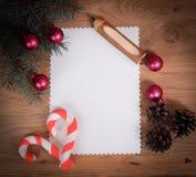 Den tomma julkortet, sörjer kottar och ritar på träbackgroun Arkivbild