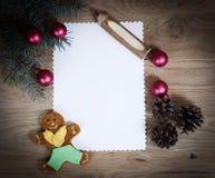 Den tomma julkortet, sörjer kottar och ritar på träbackgroun Royaltyfria Bilder