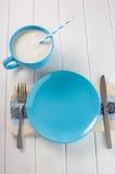 Den tomma keramiska plattan och mjölkar i en kopp på den vita trätabellen Arkivbilder