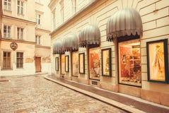 Den tomma kullerstengatan med shoppar fönster på historiska byggnader Arkivfoton
