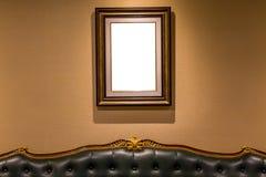 Den tomma lyxiga fotoramen som hänger på väggen ovanför soffan, int Fotografering för Bildbyråer