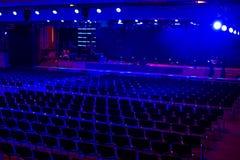 Den tomma mörka moderna korridoren för händelser och presentationen med etappen och blått tänder Preperation för ceremoni i proce royaltyfri fotografi