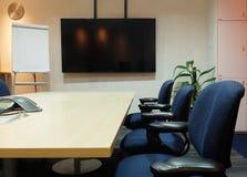 Den tomma mötesrummet med konferenstabellen, ergonomiska stolar för tyg, den tomma skärmen och tomt papper Flip Chart som används Royaltyfri Bild