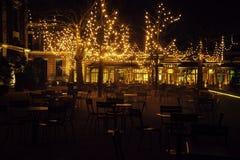 Den tomma nattrestaurangen, lotten av tabeller och stolar med ingen, magiska felika ljus på träd gillar jul Royaltyfri Bild
