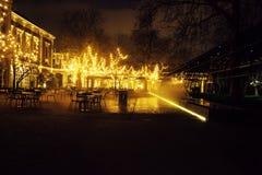 Den tomma nattrestaurangen, lotten av tabeller och stolar med ingen, magiska felika ljus på träd gillar jul Royaltyfri Foto