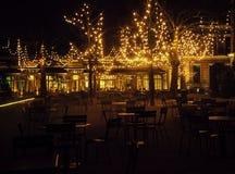 Den tomma nattrestaurangen, lotten av tabeller och stolar med ingen, magiska felika ljus på träd gillar jul Arkivfoto