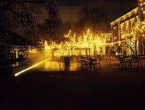 Den tomma nattrestaurangen, lotten av tabeller och stolar med ingen, magiska felika ljus på träd gillar jul Arkivbild