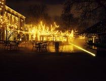 Den tomma nattrestaurangen, lotten av tabeller och stolar med ingen, magiska felika ljus på träd gillar jul, lyx Arkivfoton