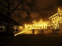 Den tomma nattrestaurangen, lotten av tabeller och stolar med ingen, magiska felika ljus på träd gillar julberöm Arkivfoton