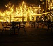 Den tomma nattrestaurangen, lotten av tabeller och stolar med ingen, magiska felika ljus på träd gillar julberöm Royaltyfri Foto