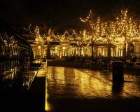 Den tomma nattrestaurangen, lotten av tabeller och stolar med ingen, magiska felika ljus på träd gillar julberöm Royaltyfri Bild