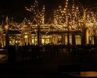 Den tomma nattrestaurangen, lotten av tabeller och stolar med ingen, magiska felika ljus på träd gillar julberöm Royaltyfria Bilder