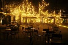 Den tomma nattrestaurangen, lotten av tabeller och stolar med ingen, magiska felika ljus på träd gillar julberöm Fotografering för Bildbyråer