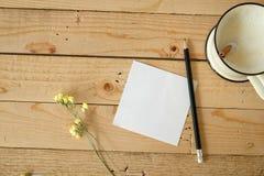 Den tomma pappers- anmärkningen och en kopp av nytt mjölkar Arkivbild