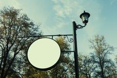 Den tomma runda skylten som annonserar, informationsbräde på pol i, parkerar royaltyfri fotografi