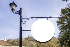 Den tomma runda skylten som annonserar, informationsbräde på pol i, parkerar royaltyfri foto