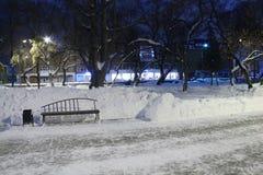 Den tomma stenvägbanken, bänken och vitt insnöat parkerar på vintern Royaltyfria Foton