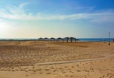 Den tomma stranden med solmarkiser och en volleyboll förtjänar arkivbild