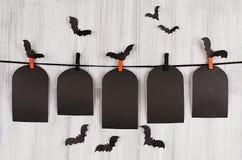 Den tomma svarta försäljningen märker gravvalvet som hänger på klädnypor med flockslagträn på vit träplankabakgrund Royaltyfri Fotografi