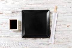 Den tomma svarta fyrkanten kritiserar plattan med pinnar för sushi på träbakgrund B?sta sikt med kopieringsutrymme royaltyfri bild